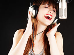 A girl with headphones on, singing into a microphone