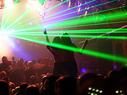 A group of people in a nightclub with green strobe lights and two girls on a table