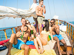 A group of men and woman drinking and laughing on a boat