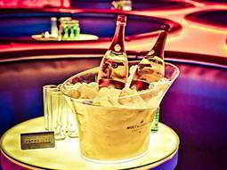 Two champagne bottles in a bucket filled with ice, with leather booths visible in the background