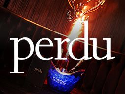 A bottle of Ciroc lit up among other bottles on a table, with the Perdu logo overlapping