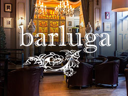 A seating area with chandeliers in the background and a logo of Barluga overlapping
