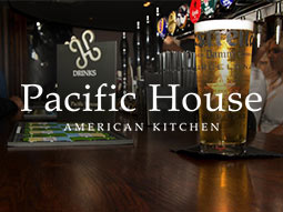 A pint on a bar, with a drinks menu in the background and the Pacific House logo overlapping