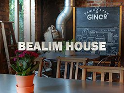 A table and chairs and a blackboard in the background with a distillery diagram on, with the Bealim House logo overlapping