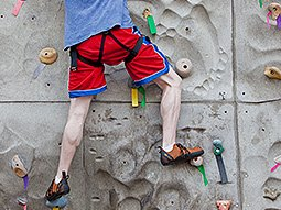 A man climbing on a climbing wall wearing red shorts