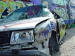A smashed up car against a graffitied wall
