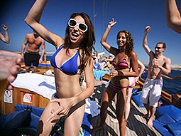 Some young people wearing swimwear, partying on board a boat