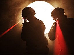 Two silhouettes of men firing lasers