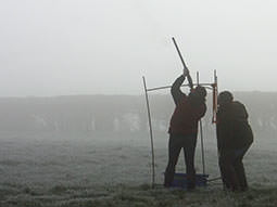 The back of a man aiming a shotgun to the sky with an instructor looking on to the side of him, to a foggy backdrop