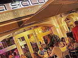People sat on outdoor seating outside La Sala at night