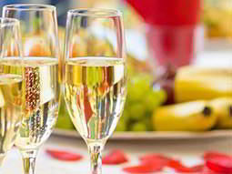 two full champagne flutes with fresh fruit in the background. Champagne Breakfast.