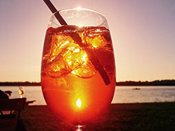 A cocktail in the foreground and a beach in the background, at sunset