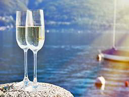 Close up of two full champagne flutes on a rock, with the sea, buoys and a boat in the background