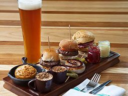 A tray with a a selection of burgers and drinks on, as well as a tall glass of beer