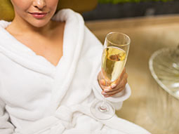 A woman in a bathrobe, holding a glass of alcohol
