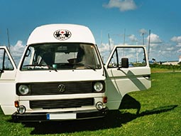 A white VW Bulli Limo parked up in a field