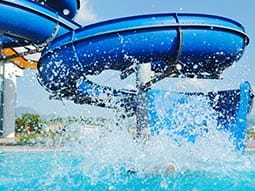 A blue water slide with lots of water splashing at the bottom