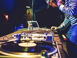 A DJ with a cap and headphones, at a mixing desk
