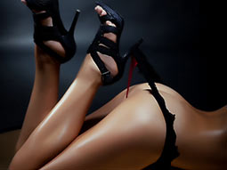 A close up of a womans legs and bottom, wearing a thong and heels