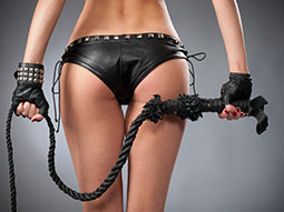 the back of a women wearing leather pants and holding a whip
