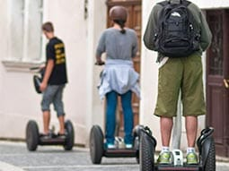 Three people going down a street on segways