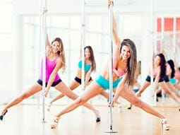 A group of woman in shorts and vest and high heels holding on to poles on a wooden floor and doing the splits