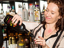 A woman pouring a drink into a glass, with bottles of alcohol behind her