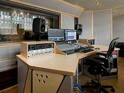 A recording studio desk with speakers, amplifiers, screens and a sound mixing desk