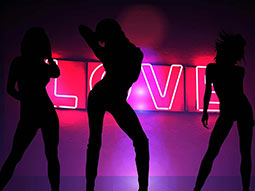 A silhouette of three women on a backdrop of the word 'love' in neon lights