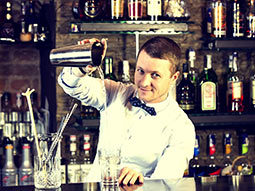 A man behind a bar pouring a drink into a glass from a cocktail shaker