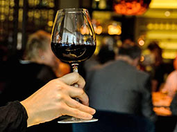 A close up focusing of someone holding a glass of red wine, with some people in the background