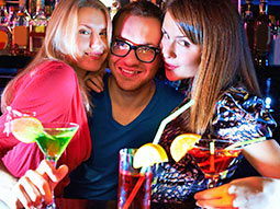 Two women and a man posing next to each other in a bar, with drinks in their hands
