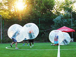 A group of people in inflatable zorbs on a pitch