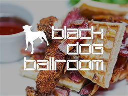 A chicken and bacon waffle with a dip and the Black Dog Ballroom logo over the top