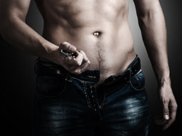 A close up of a topless man, with his belt and jeans undone
