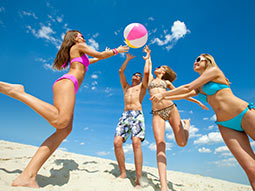 A group of people trying to hit an inflatable ball on a beach