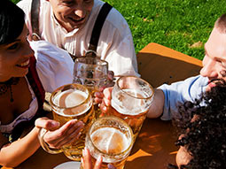 A group of people sat outside on a bench with a pint of beer each in their hands