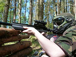 A person dressed in camouflage holding a paintball gun in a forest