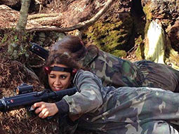 Two people crouching down in camouflage suits, with guns
