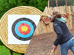 A split image of an archery target and someone throwing an axe at a target