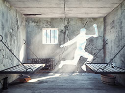 A prison cell room with a cut out of a person in the wall