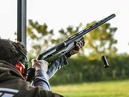 A man firing a black shotgun into the sky