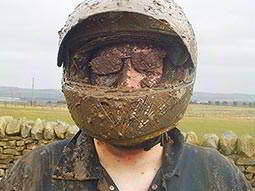 A man in a mud covered helmet
