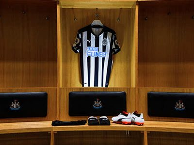 An NUFC shirt hanging up with a pair of shorts and trainers on a shelf below