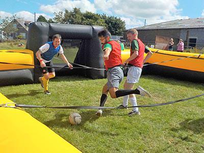 Men standing in a large inflatable football pitch, tethered to ropes and playing football