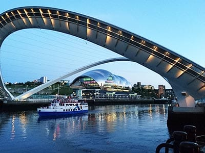 A large blue and white pleasure boat on the River Tyne