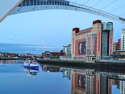 An image of a blue and white boat sailing under the Millennium Bridge on the River Tyne