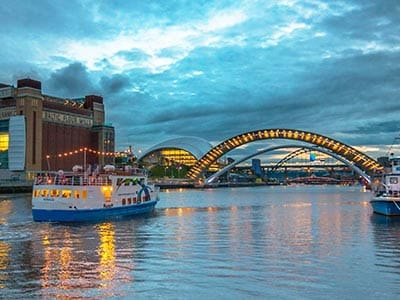 A blue and white pleasure boat on the River Tyne, with the Millennium Bridge, Sage and Tyne Bridge in the background