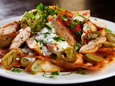 Nachos topped with chicken and served up on a white plate