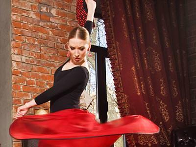 A woman wearing a flamenco skirt, dancing indoors